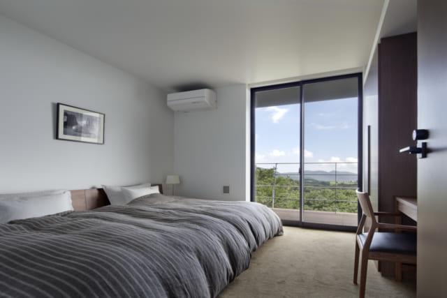 広々としたベッドが置いてあるシンプルなベッドルーム。窓は敢えて片側だけの設計とし、朝日が登るとともに心地よく目覚めるつくりになっている