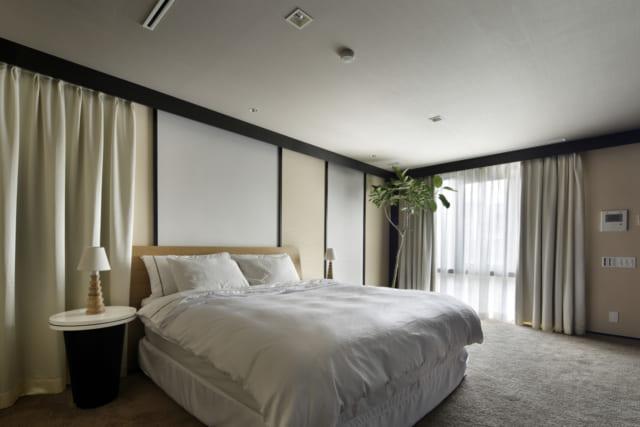 スクリーンや絨毯を敷くことで、どこかリゾート地を思わせる雰囲気のベッドルーム。枕元のランプなど、アジアンなリゾート気分を演出している