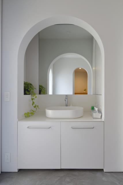 玄関を入ってすぐの共用スペースに洗面所を置くことで、家族にも来客にも使いやすい場所となった。鏡に映ったアーチが連なり美しい