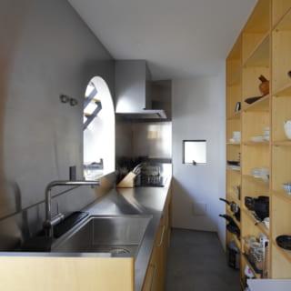 キッチンは、ステンレスでシンプルかつスッキリと。リビング家具と統一されたオリジナルな棚で見せる収納を実現