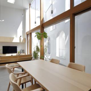 高い天井と窓から白壁に反射する奥庭からの明るい日差し、統一された木の家具に彩られたリビングは、まるでオープンカフェにいるよう