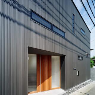 建築事務所の入口は東側。外壁材にガルバニウム鋼板を用いることで、木製ルーバーで覆われた住宅部とは異なる印象に