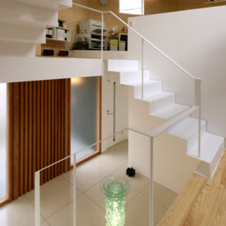 住居スペースと高さレベルが違うため、事務所は吹き抜けの階段を中心に半層ずつずらすようにワークスペースや資料室を配置