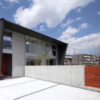 住宅の外壁材はガルバニウム鋼板。クールな印象に合わせて、駐車場はコンクリートの打ちっぱなしで仕上げた