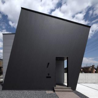 西側、真横より見た外観。ゲート状の大屋根と横壁が南面に傾いている。黒とシルバーの組み合わせもクールな印象