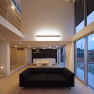 夜のLDK。照明計画はダウンライトと壁の間接照明でシンプルに。無垢のフローリングは明るい色目のバーチを使用する