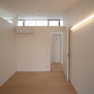 子ども部屋の壁上部に設置されたスリット窓を通して、住宅北側のハイサイドライトが見え、十分な採光を得ることができる