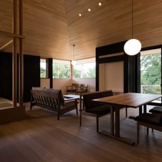 大屋根の下に広がるLDKが家の中心。腰壁の前、リビング、ダイニング、小上がり、デッキの前と多彩な居場所を提案