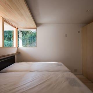 南角に位置する寝室。天井より仕切壁を低くすることで、先にも部屋があることを示唆して、空間に広がり感を持たせている