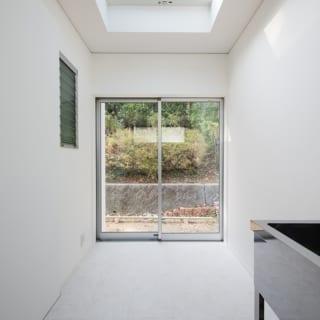 白を基調とした明るいサンルーム。南側は外に出られるよう掃出し窓に。トップライトから光が注ぎ、洗濯物もよく乾く