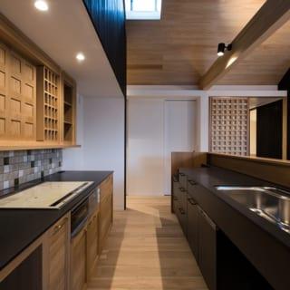 夫婦二人には十分すぎるほど大きなキッチン。両面ともに引出し収納をたくさん設けたほか、上部に作り付けの収納棚も設置