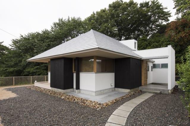 シルバーの大屋根を、黒いボックス状の壁が支える構造。天井の檜の羽目板が水平に外部へと張り出し、庇となっている