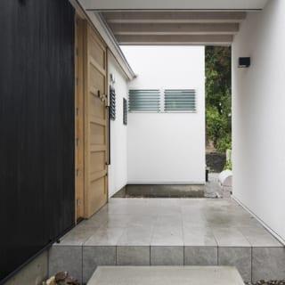 コンクリートブロックの飛び石を経て玄関にアプローチ。一段上がったポーチと玄関内はタイル敷に。黒壁は塗装仕上げだ