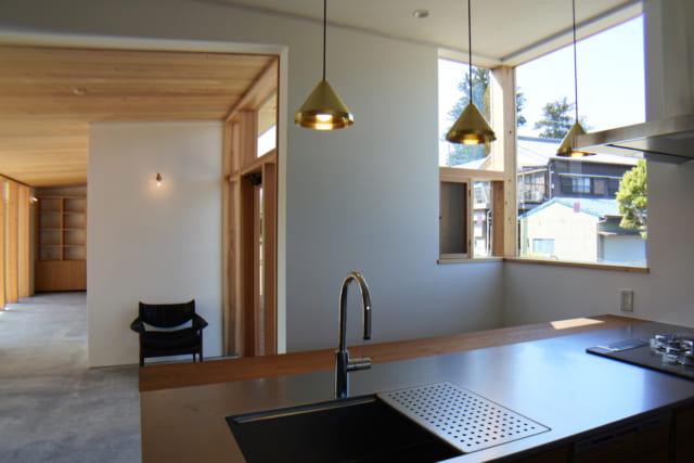 開放感あるオープンキッチンはチーク材を使用して造作。コンクリートの土間のホールやダイニング空間を見渡せる