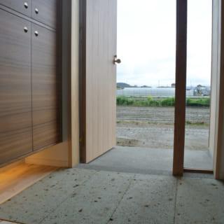 扉一枚を隔てて、のどかな周囲の景観と繋がっているかのような玄関。足元を間接照明で照らした玄関収納は造作