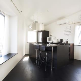 3階 キッチン/上原さんが「贅沢な配置」だというキッチン。実際に立ってみると、空間全体を見渡せるばかりか出窓の景色も楽しめる、ゆとりのあるつくりになっている。LDKは落ち着いた雰囲気で重厚感も出したい、とのご希望から床を黒にし、キッチンの立ち上がり部分や背面の造作棚も同じ色合いに