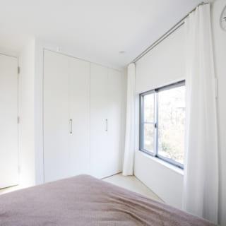 2階 主寝室/周りの住宅もほとんどが3階建てのため、3階に比べると光が採りにくい2階は床の色も含めて全体的に白いイメージにした。収納は主寝室を優先的に、という理由で豊かなクローゼットをドアの両側に配置している