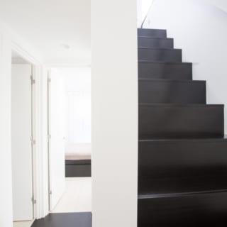 2階 廊下/白と黒の使い分けの妙は内部空間でも見られる。1階、2階ともに階段や廊下といった共有部分は黒、部屋などプライベートスペースは白。メリハリのきいた空間の演出からは、暮らしやすさや快適さを考慮した内部空間と、エッジの効いた外観とが一つの線でつながっているのを感じる