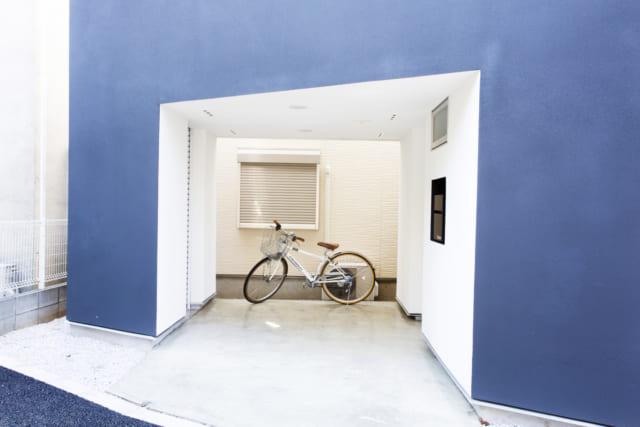 1階 ガレージ(ポーチ)/車一台すっぽり収まるサイズのガレージ(ポーチ)。左側は外部倉庫になっており、キャンプ用品など大型用具の出し入れが車と直にできる。右壁面の窓は浴室のもの。浴室がこの位置にあるのも、変形敷地に建つ家ならでは