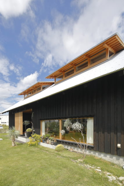 杉板貼りの外壁に、柿渋と松煙を使った黒塗りで風合いを出した外観デザイン。のどかな周囲の風景に溶け込んでいる