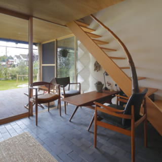 階段下の広いホールは応接間のような設えに。インナーテラスから庭へと繋がる空間の広がりがあり、開放感あふれる
