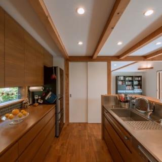 広々としたキッチン。ステンレストップのシンク&コンロの背後に棚を造作し、脇にパントリーも設け収納力を高めている