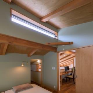 2階にある寝室。ハイサイドライトによる採光と通気で心地よい空間に。寝室隣には収納スペースを設けた