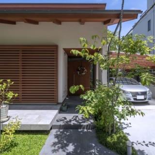 玄関へと続くアプローチにはテラスと色の異なるタイルを貼った。駐車場は予算を考慮しコンクリートを打っている