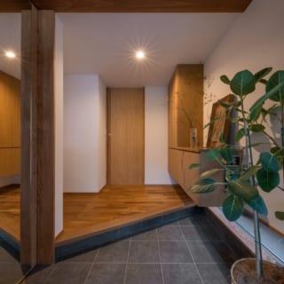 玄関の土間はアプローチやテラス同様にタイル仕上げ。玄関土間の脇には収納スペースが設けられている