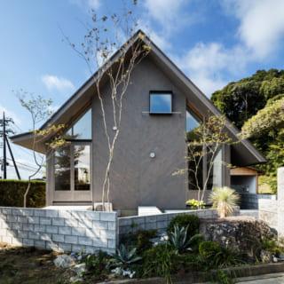 のどかな里山の風情あふれる環境に馴染む造形の外観。大きな三角屋根、外壁の両端がガラス張りになった独創的なデザイン