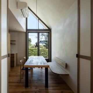 窓際のダイニングスペース。大屋根の形状を利用した勾配天井で、大きな三角形のガラス窓が特徴的