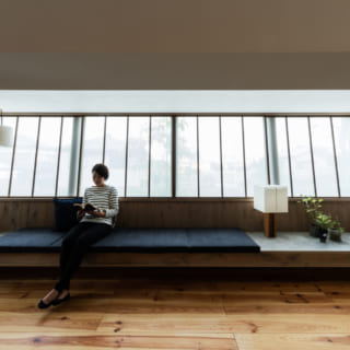 南東側のリビングスペースには大きな窓を設け、吹き抜けを通して2階へと光を届けている。広々とした造作のソファでゆったり寛げる