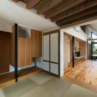 """リビングを望む畳敷きの和室。天井には化粧梁を、また昔の床の間の違い棚をモチーフにした""""違い戸""""の吊り収納も造作"""