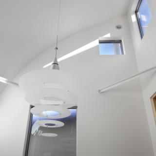 上から入る光が1階まで反射して届くように湾曲してつくられた天井。デザイン的にも空間に変化を与えている