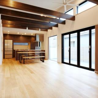構造材の梁をあえて見せることで天井を高くとり、空間の広がりを演出。大開口からの光が室内を明るく照らす