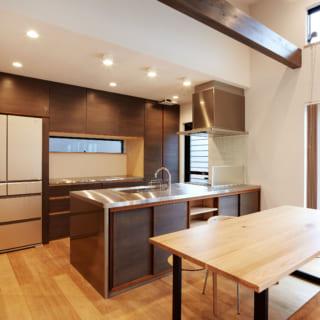 天井の梁と色を合わせたキッチン。調理をしながらリビングの様子が見渡せる