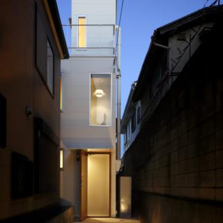 夜の外観。細長い路地をイメージしたアプローチを進むと、白い建物の外観が見えてくる。旗竿地であることもA邸の1つの魅力