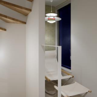 階段を上がったところにあるくつろぎスペース。お洒落なクロスとチェア、照明をしつらえ、小さいながらも部屋のようなスペースをつくりあげた