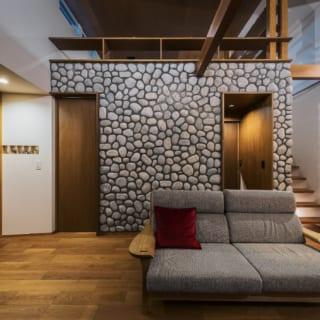 ロフト側の壁一面に貼った石模様のタイル。トイレやバスルームなど水回りはこのロフト下にまとめて配置した。