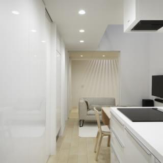シンプルに白で統一した使い勝手の良いアイランドキッチンは、今回造作したもの。後ろの扉を開けると1畳半ほどのパントリーも備えている