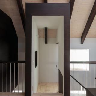土間から伸びる階段は、途中で直角に折れて2階へ。真っ直ぐ伸びた階段の最上部には、転落防止用の扉が設けられている