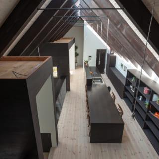 切妻屋根のシンプルで大きな家のなかに、小さな箱を設ける要領でリビングスペースや子ども部屋をデザインしている。箱の上部に照明器具をのせて間接照明として利用