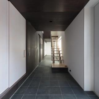 玄関から入るとすぐゆとりある土間が広がる。黒と白を基調とした陰影のあるシックな趣。吹き抜け階段で2階とつながる