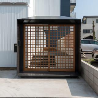 奥さまがこだわった、和を意識した門は9ミリの鉄板製。格子戸は水に強いレッドシダー。黒い重厚感ある門構えと白い建物とのコントラストが印象的
