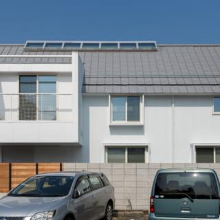 南側の駐車場から見た外観。2階天井にひと連なりの天窓が設けられていることがわかる。屋根はシルバーのガルバリウム鋼板