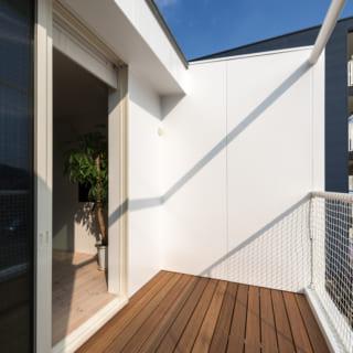 2階バルコニーは玄関の庇も兼ねる。足元のデッキ材はセランガンバツ。隣に建物ができても揺れ防止のバーを使い目隠しが作れる