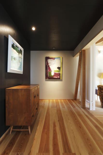 ダイニングとリビングをつなぐギャラリースペース。正面と左手に飾られている絵画もKさんお気に入りの岡野博氏の絵画作品。右手に見えるのは除湿型放射冷暖房(ピーエス)。ちなみにこの家では次世代省エネ基準をクリアする性能を確保した上で、ここと寝室の2箇所に放射冷暖房を設置し、主な生活スペースの環境を穏やかにコントロールしている