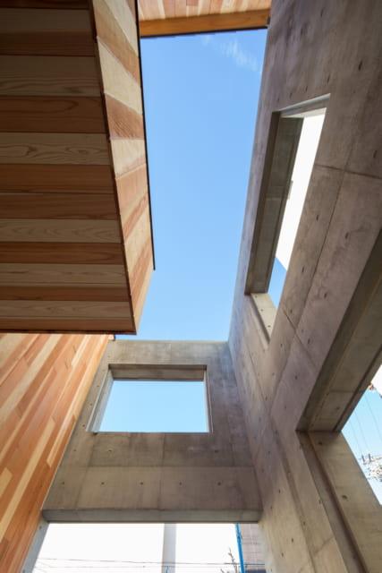 コンクリート外壁と木造建物の中間領域から空を見上げた様子。コンクリートとレッドシダー材のデザインバランスが美しくマッチしている