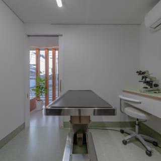 清潔感あふれる診察室。患者とスタッフの動線を完全に分離。仕切りの壁も構造的な役割を担っている