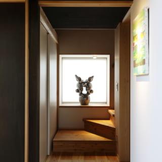 2階に上がる階段前のスペース。天井を低く抑えて落ち着いた雰囲気に。正面の出窓は河井寛次朗作の兎の像の大きさに合わせサイズを決定した。ちなみに小さな壁にも絵画を飾ることを想定した照明が用意されている